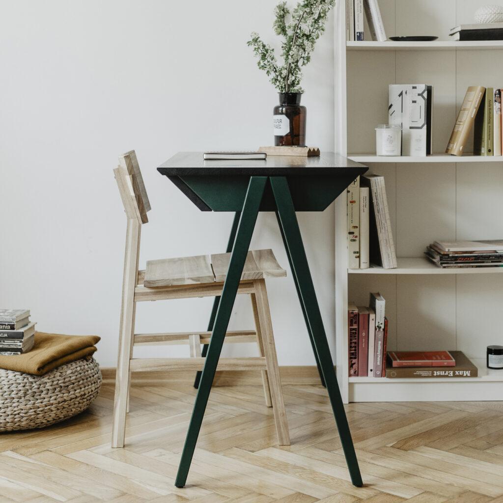 drewniane biurko z czarnym dębowym blatem oraz z drewnianymi zielonymi nogami