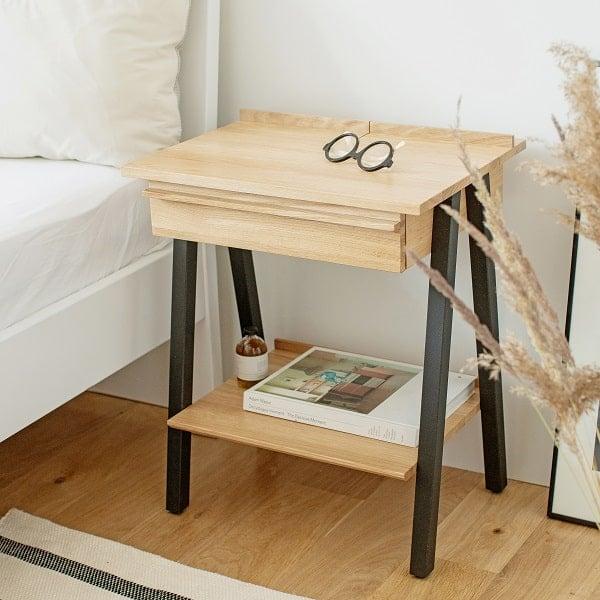Szafka nocna czarna troost z litego drewna w aranżacji sypialnianej przy łóżku